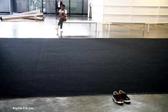 Alguém deixou os sapatos para não sujar o tapete onde são feitas apresentações artísticas, mas que acabou sugerindo obra de um artista