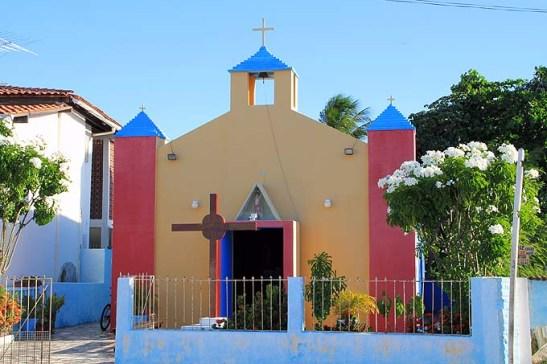 uma capela colorida no vilarejo com pousadas, hotéis e restaurantes