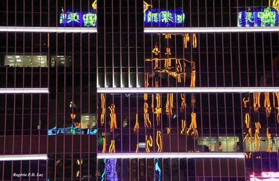 os reflexos de luzes fragmentadas numa fachada envidraçada