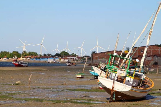 Em maré baixa barcos ficam encalhados.  Ao fundo, novo parque eólico da Petrobrás.