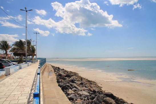 Muralha de pedra na praia tenta conter fortes erosões devido a combinação de marés e ondas fortes. A região como o município de Macau venta muito, bom para as salinas e o funcionamento de eólicas para gerar energia, mas também tem seu preço.