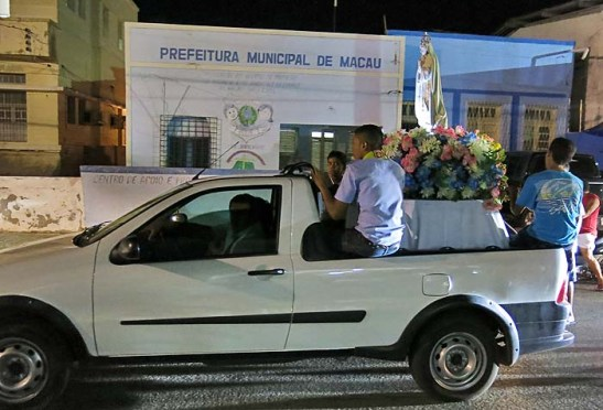 A procissão com N.S. de Fátima em cima da camioneta e acompanhado por fiéis a pé e de carro pelas ruas da cidade.  Na foto, o carro passa diante de uma unidade da Prefeitura de Macau.
