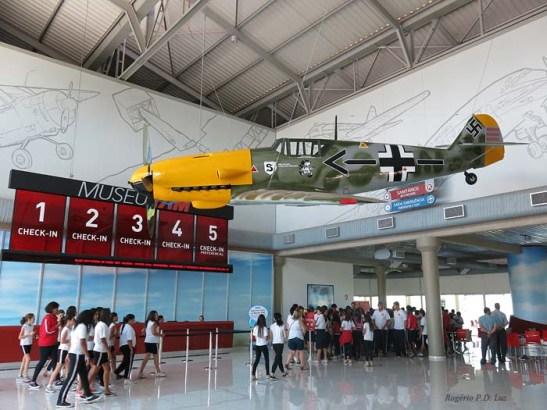 """Museu TAM.  Os balcões """"Check-in"""" para compra de bilhetes lembrava um aeroporto e já se via exposto um Messerchmitt da 2ª Guerra. Caravanas de escolares faziam visitas monitoradas para alegria da criançada."""