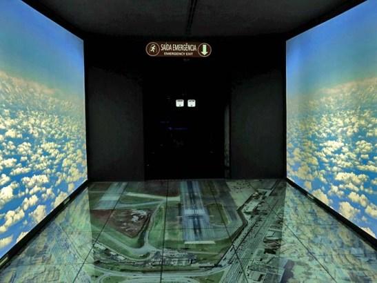 O primeiro acesso é por um corredor cultural, antes passando por um ambiente com nuvens dos dois lados e pisando sobre a fotografia do Aeroporto de Congonhas de São Paulo.