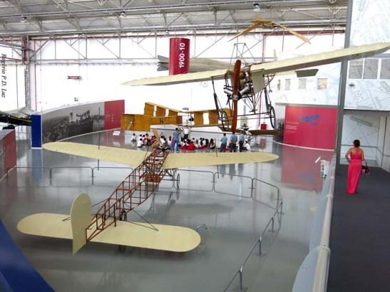 A rampa ao lado para acesso ao local de exposição.  Vê-se ao fundo escolares recebendo informações de monitores diante de uma réplica do 14 Bis do pai de aviação Santos Dumont