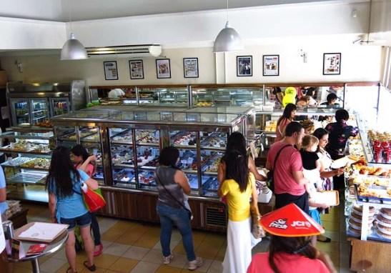 """O interior da padaria com grande variedade de pães, salgados e doces.  Até tem """"poló páu""""."""