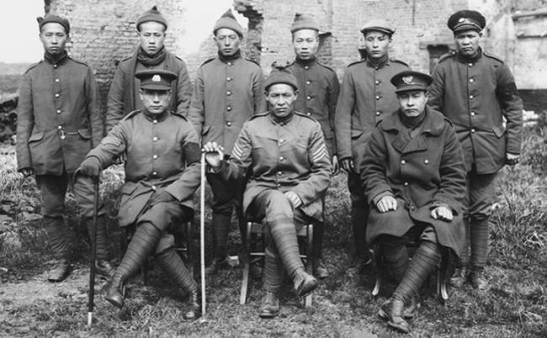 Nove integrantes da Corporação de Trabalhadores Chineses em uma casa em ruínas. Entre eles dois gangers e um intérprete.  (In Flanders Fields Museum, Ypres)