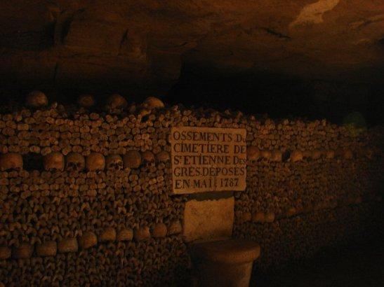 - Interior das Catacumbas de Paris. Placa indicando o local dos despojos oriundos do cemitério de Saint Etiénne (Wikimedia Commons)