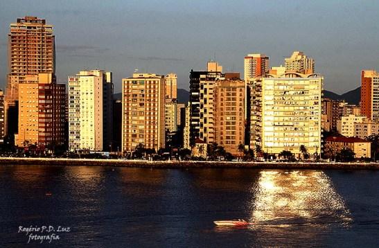 Prédio em Santos reflete a luz do sol na água em fim de tarde
