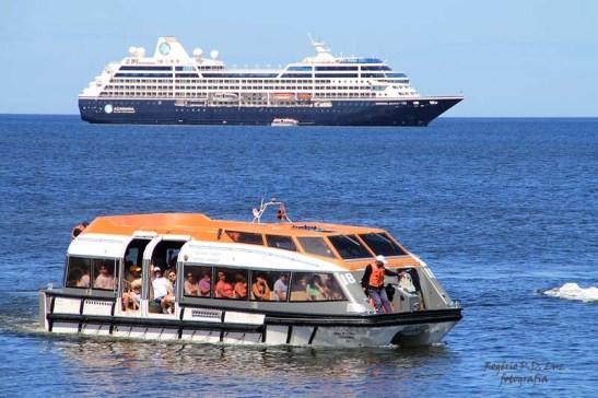 O barco auxiliar/tender ou barco salva-vidas, tendo ao fundo outro navio de cruzeiro.