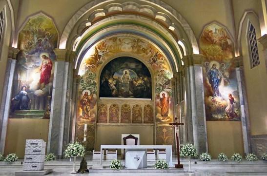"""""""Em 1951, Aldo Locatelli inicia as pinturas da Igreja com o mural da Santa Ceia, de 90 metros quadrados de área, ladeada pela Aparição do Sagrado Coração de Jesus a Santa Margarida Maria Alecoque, à esquerda, e a Aparição de Nossa Senhora de Caravaggio à vidente Joaneta, à direita."""""""