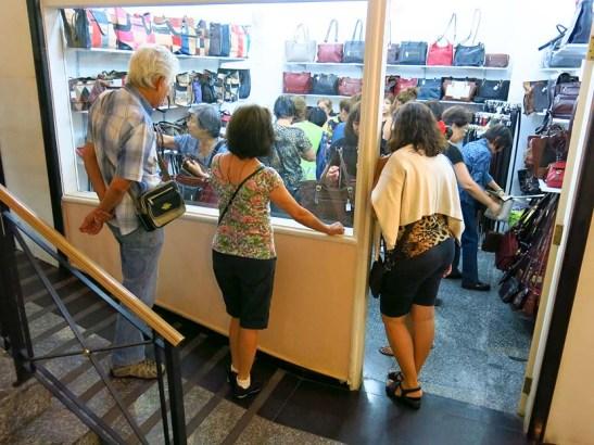 Uma parada numa galeria de lojas com uma delas a promover uma liquidação de bolsas, para alegria das senhoras excursionistas