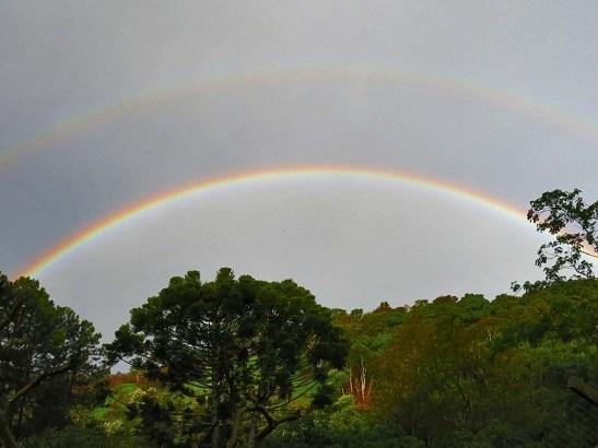 Um duplo arco-íris apresenta as cores invertidas no arco secundário (o arco superior na foto).