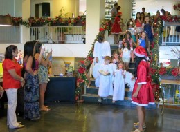 Procissão de crianças carregando a imagem de Menino Jesus