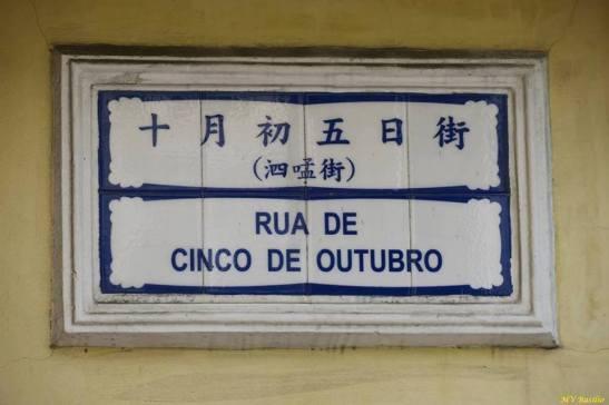 """Os três caracteres chineses que estão escritos entre parênteses na placa toponímica lêem-se """"si máng kai"""", isto é, Rua do Simão"""